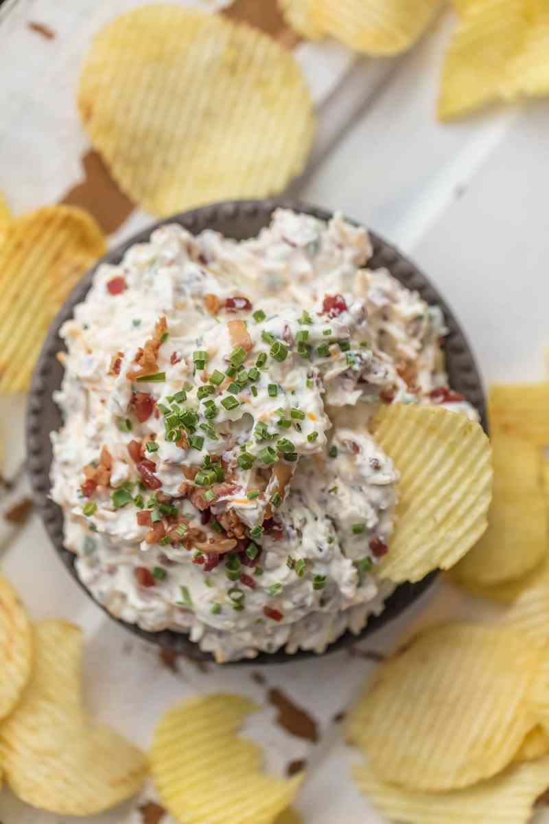 A bowl of caramelized onion bacon dip, surrounded by ruffled potato chips