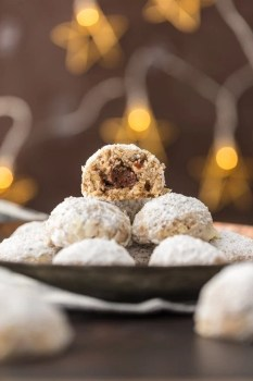 stack of NUTELLA STUFFED SNOWBALL COOKIES with a bite taken out of the one on the top