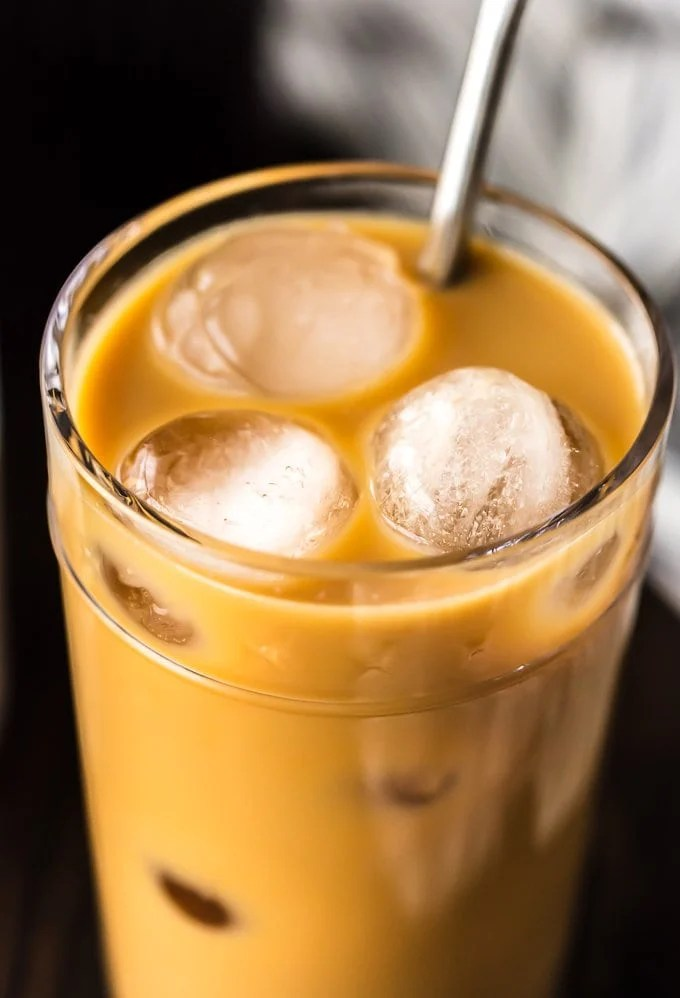 up close picture of iced coffee with cream in a glass