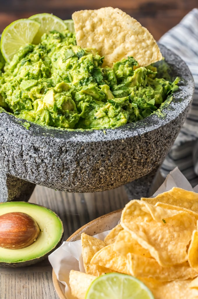 Homemade guacamole dip in a mortar & pestle, with a single tortilla chip dipped in