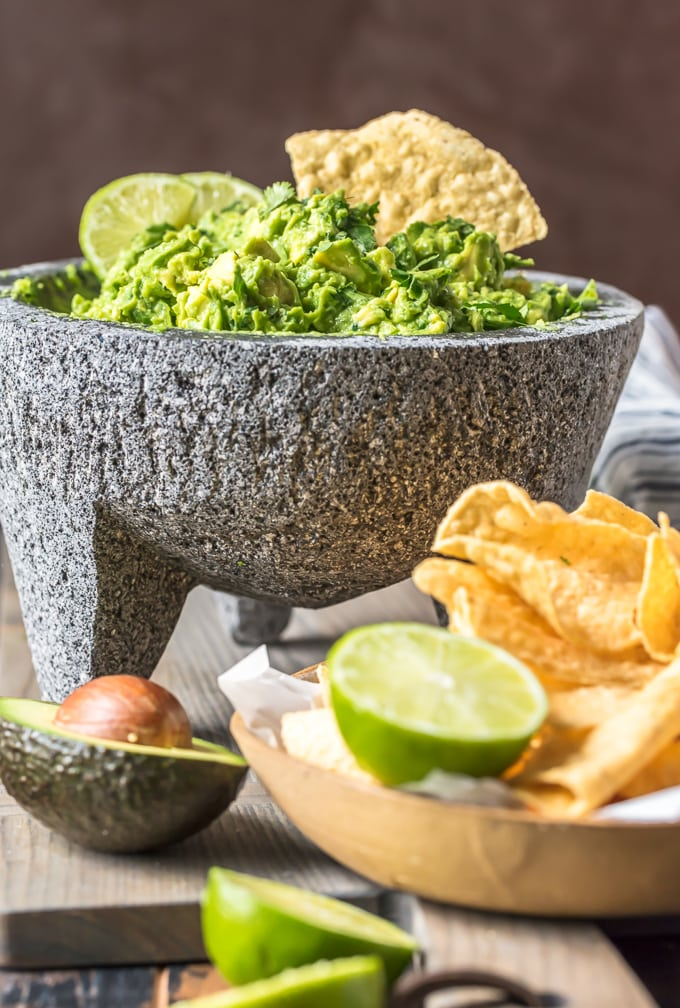 Bowl filled with guacamole next to a bowl of chips