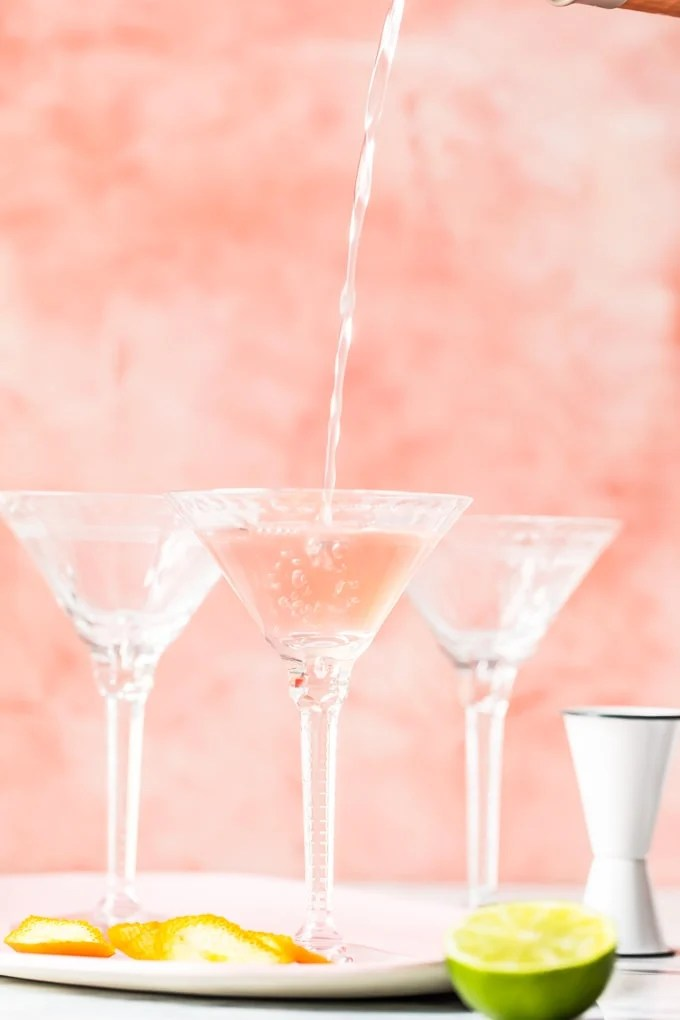 filling cocktail glasses with a cosmopolitan