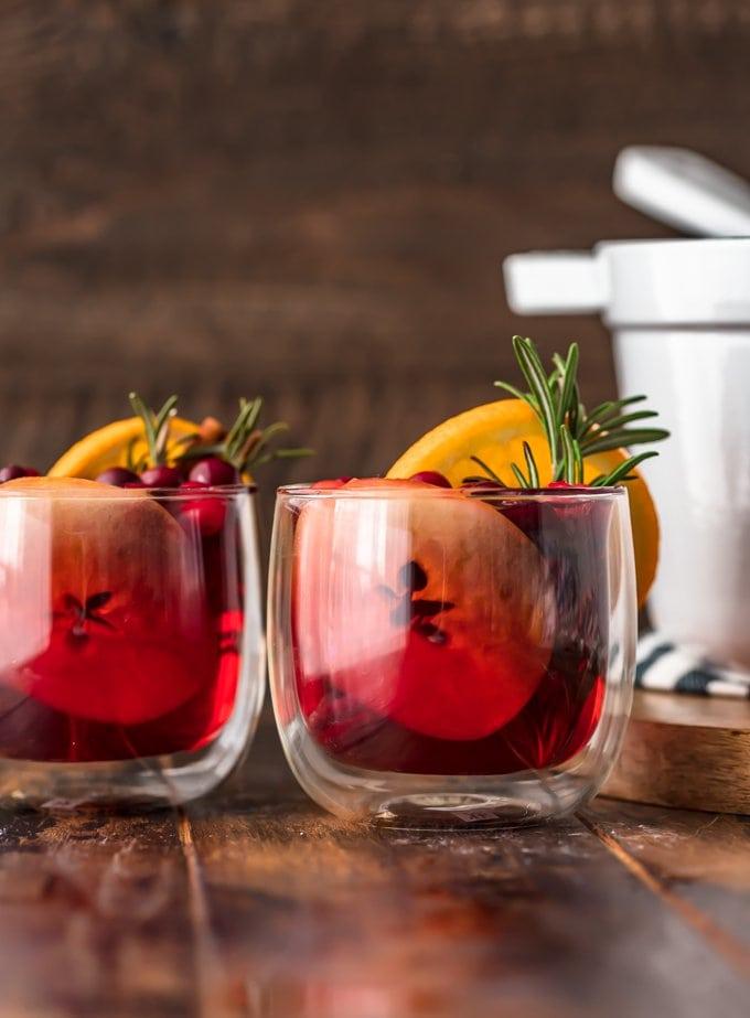 Two glasses of hot apple cider garnished with orange slices