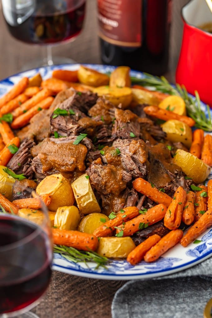 red wine pot roast recipe on a serving platter with gravy and vegetables