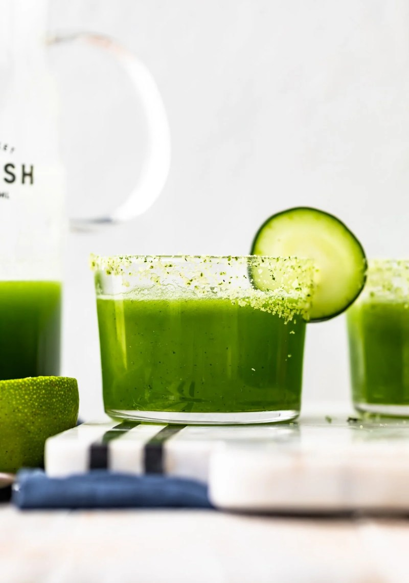 up close picture of spicy cucumber margaritas with cucumber and cilantro salt garnish