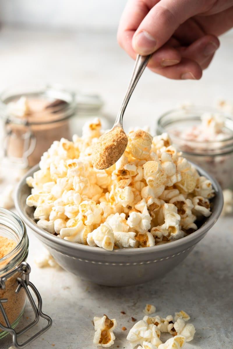 A side shot of popcorn salt getting sprinkled over popcorn