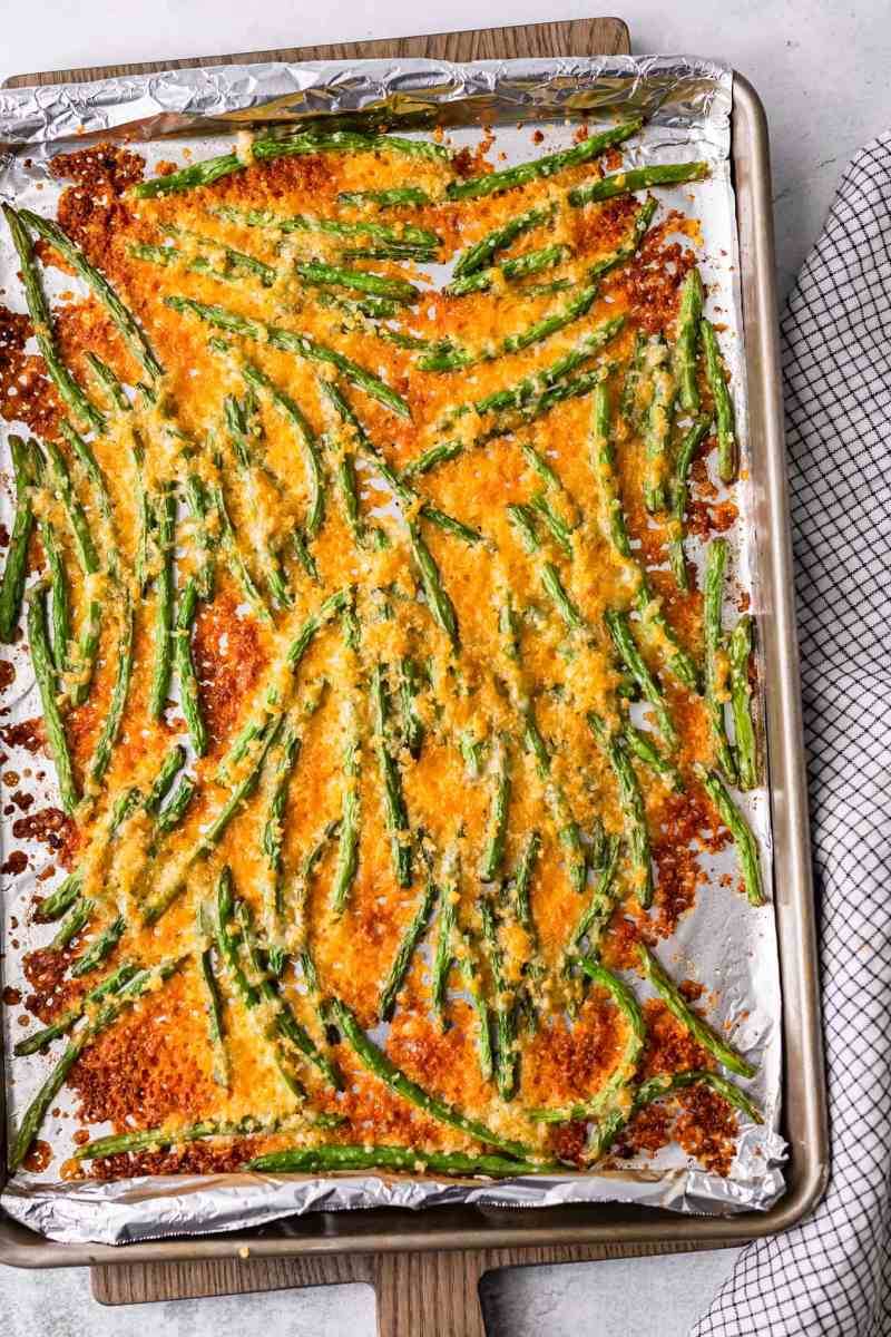 cooked green beans with cheese on a sheet pan