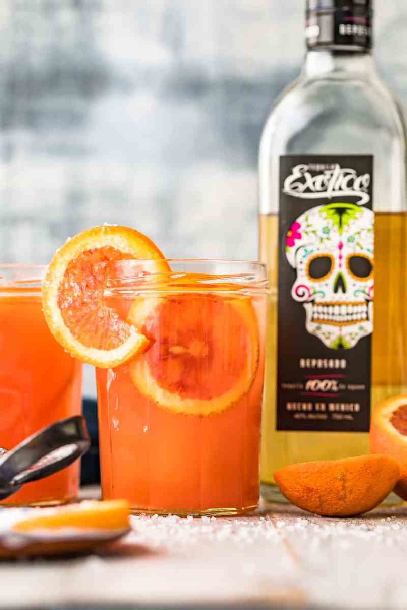 A blood orange paloma cocktail in front of a bottle of tequila