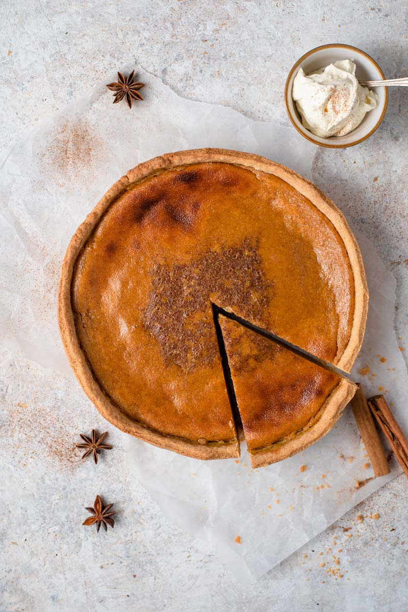 A homemade pumpkin pie with a slice cut out and whipped cream at the side