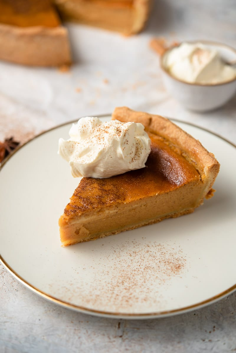 A slice of homemade pumpkin pie on a plate with whipped cream