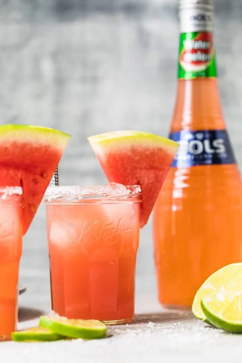 watermelon cocktail next to a bottle of watermelon liqueur