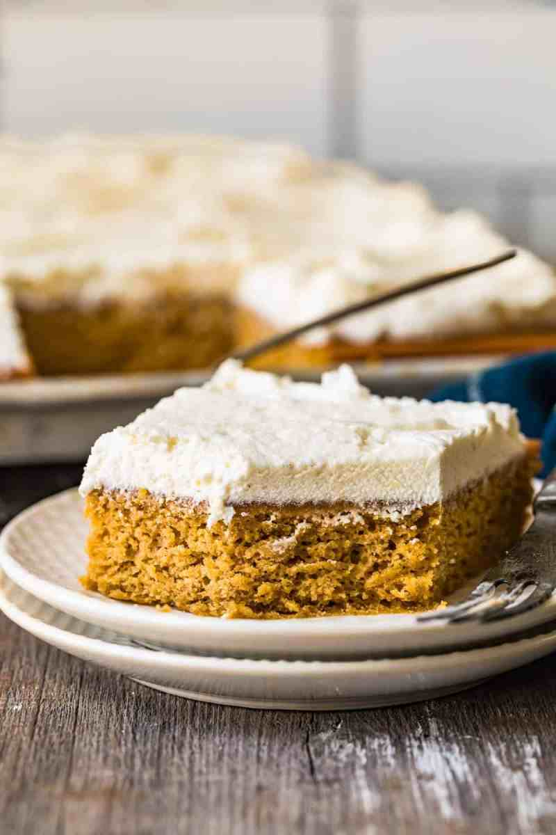 A pumpkin pie bar with icing on a white plate