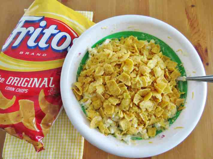 crushed Fritos corn chips added to mayonnaise dressing with yellow corn kernels, diced green peppers, onions, shredded cheddar cheese in Pampered Chef plastic bowl