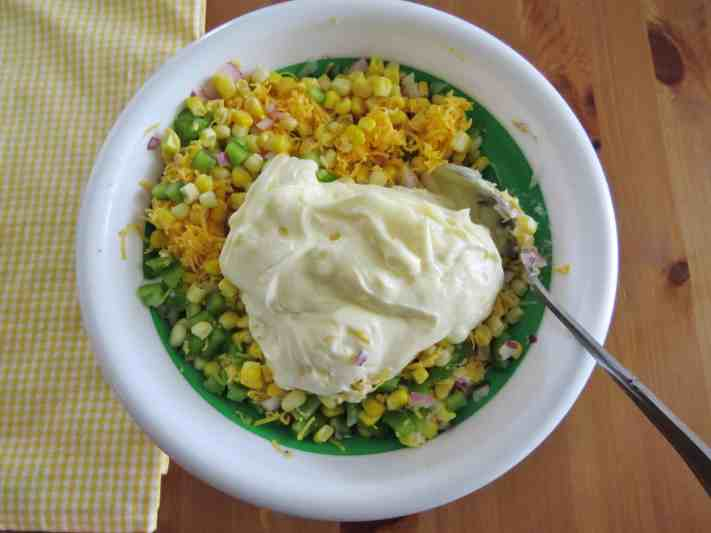 mayonnaise and taco seasoning stirred together with corn, shredded cheddar cheese, green peppers and diced red onions in a white and green bowl