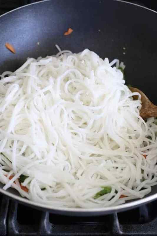 cooked rice noodles added to hot wok