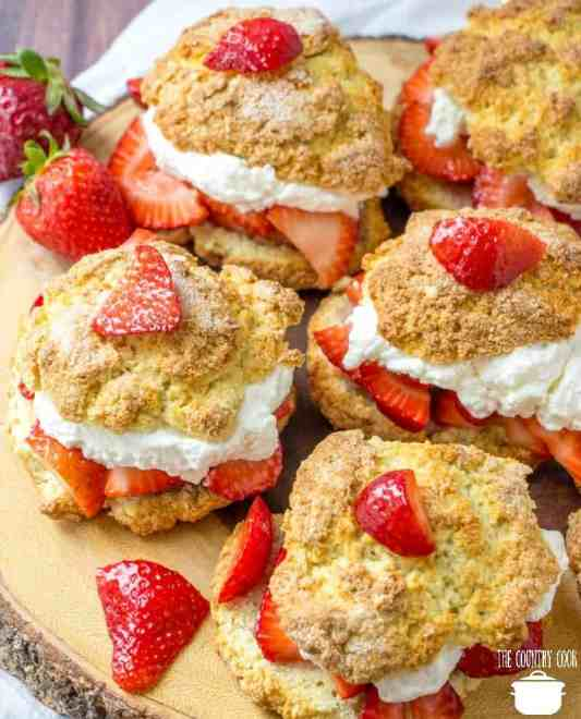 Strawberry Shortcakes with whipped cream and sweetened strawberries on a wooden board
