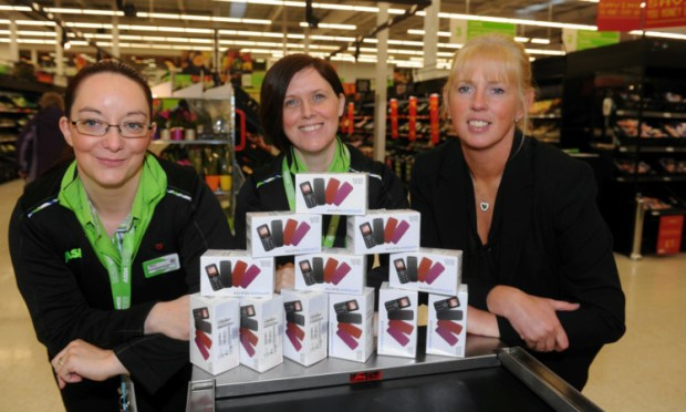 Mel Smith and Sonia MacLean from Asda hand over the mobile phones to Detective Constable Wendy Smith from Police Scotland Tayside Divisions Domestic Abuse Investigation Unit.