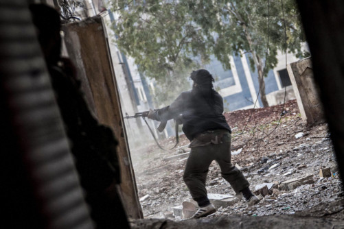 A Free Syrian Army fighter aims his weapon during heavy clashes with government forces in Aleppo.