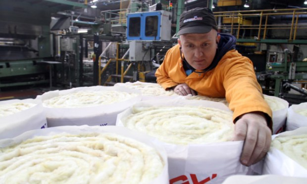 A worker inspects rolls of Superglass insulation.