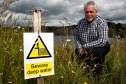 Councillor Bill Brown beside a sign warning of deep water danger at Kinglassie Quarry.