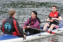 Eoin Ryan (L) and Chris Bell (R) show Gayle Ritchie how to row.