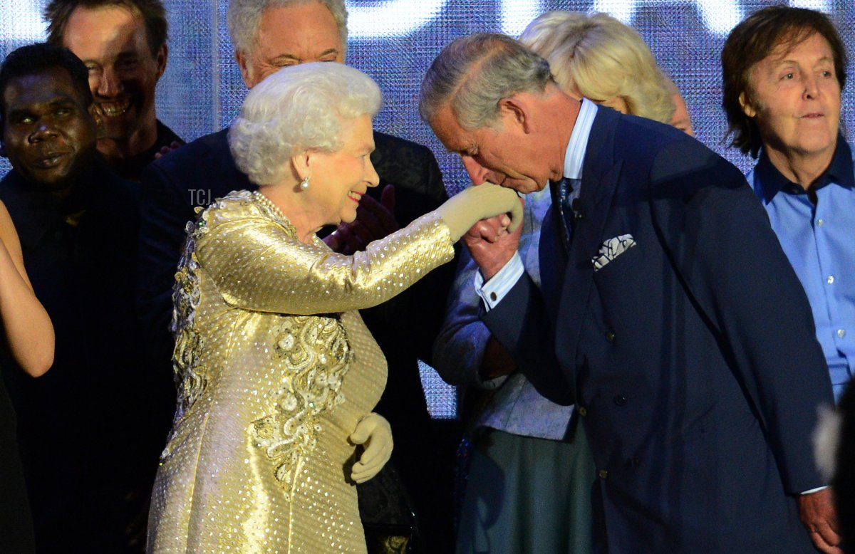 Prince Charles kisses the hand of Britain's Queen Elizabeth II on stage as well as British singer Paul McCartney (R) looks on after the Jubilee concert at Buckingham Palace in London, on June 4, 2012. A chain of more than 4,200 beacons began to flare across the globe Monday to mark Queen Elizabeth II's diamond jubilee, with the last to be lit by the monarch at a star-studded concert at Buckingham Palace