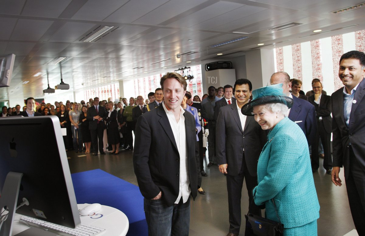 Britain's Queen Elizabeth II (2nd R) looks at a computer showing a You-Tube video alongside Chad Hurley (C), co-founder of You Tube, and Nikesh Arora (R), President of Google Europe, Middle East and Africa during a visit to the company UK headquarters in London,on October 16, 2008. An image of the Queen has been incorporated into Google's UK homepage logo to mark her visit to the internet giant's British headquarters in London