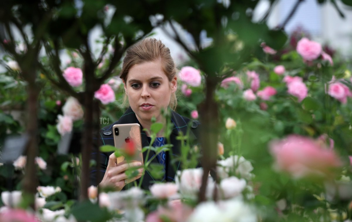 Britain's Princess Beatrice of York uses a mobile phone as she visits the 2019 RHS Chelsea Flower Show in London on May 20, 2019. - The Chelsea flower show is held annually in the grounds of the Royal Hospital Chelsea