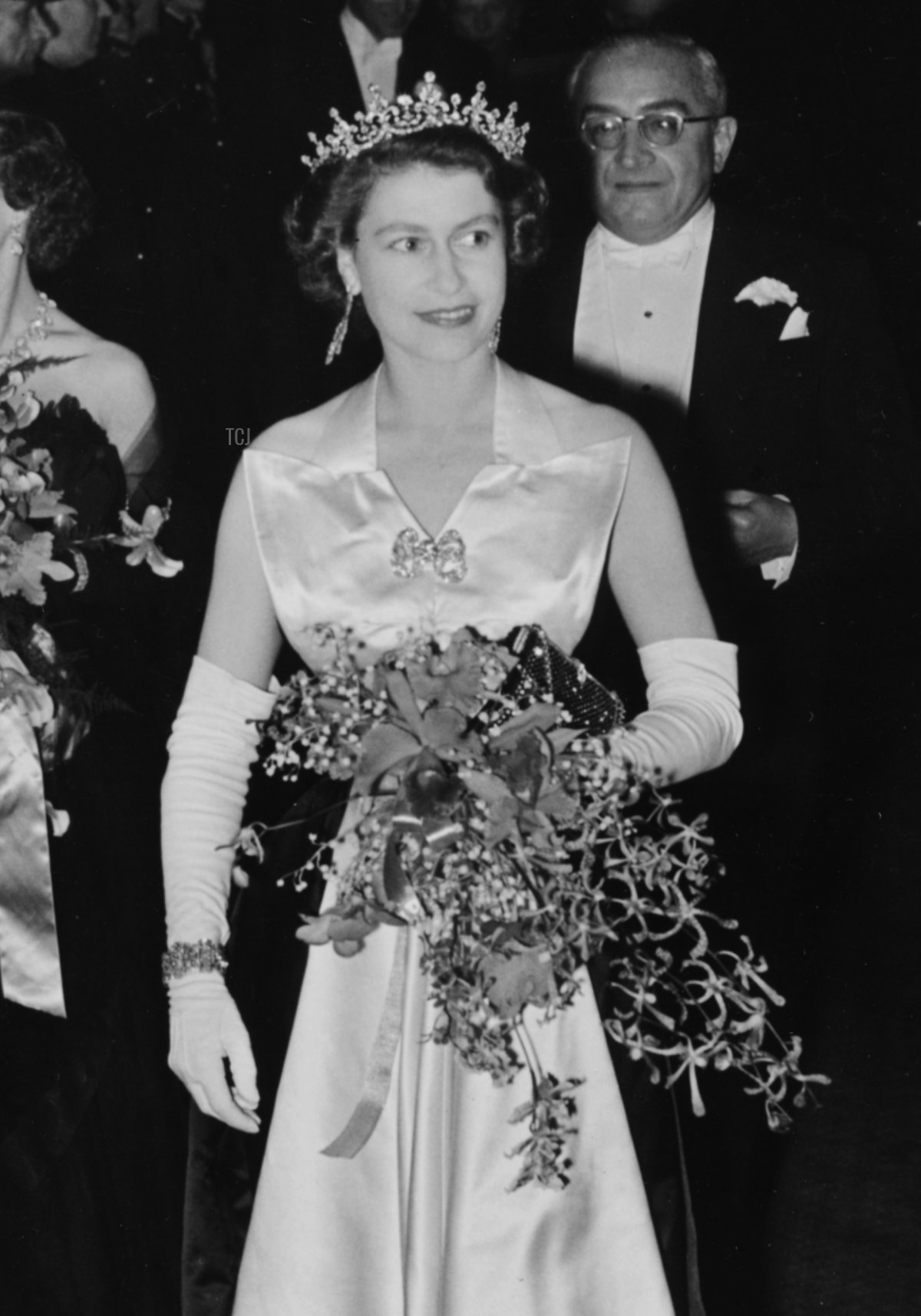 Queen Elizabeth II is escorted by Reginald Bromhead, the Chairman of the Cinematograph and Trade Benevolent Fund, as she and Princess Margaret (behind) leave the Royal Film Performance in Leicester Square, London, October 27th 1952