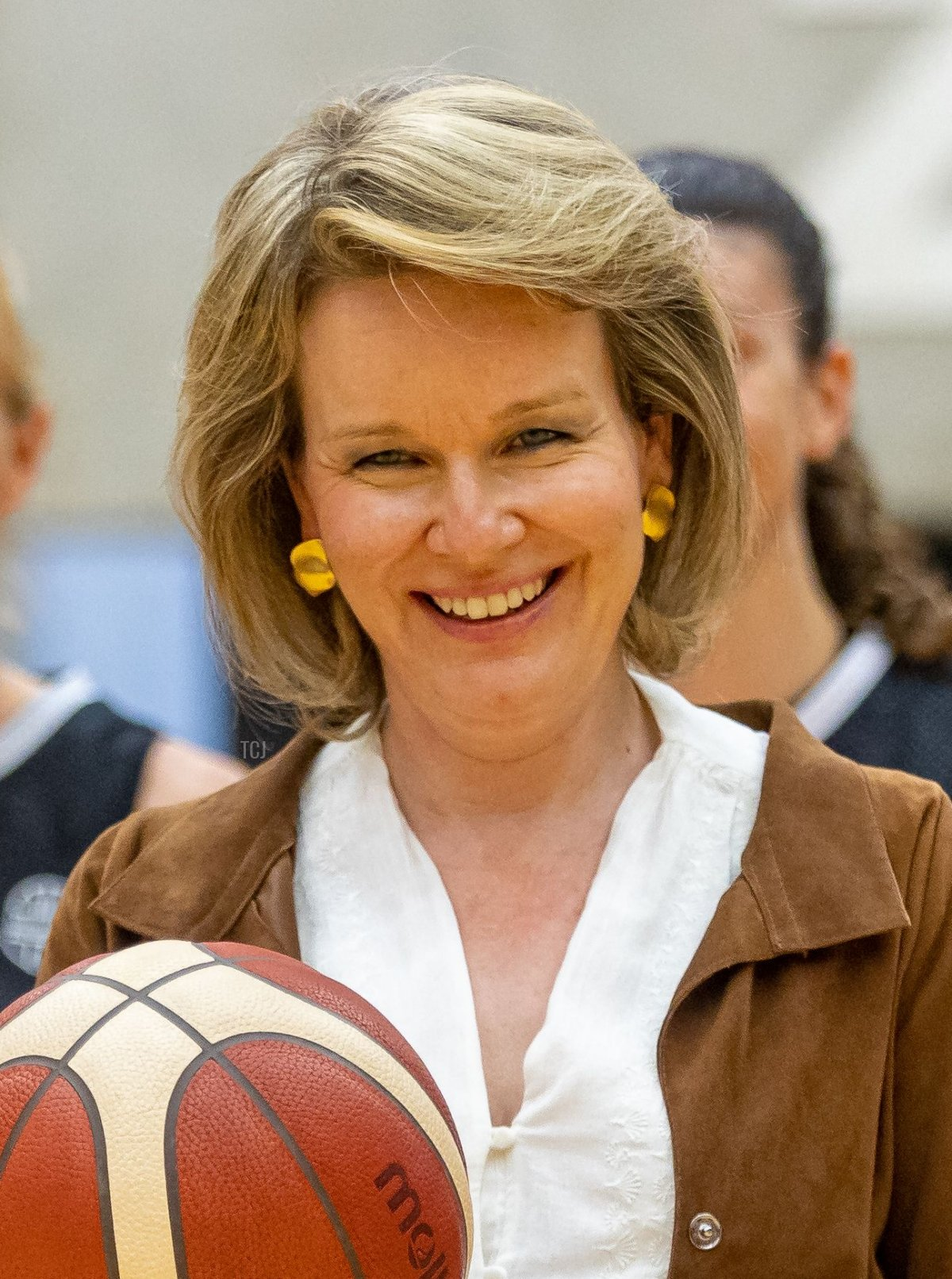 Queen Mathilde of Belgium holds a basketball during a visit to the Belgian Cats, the Belgian national women's basketball team, in Kortrijk, on June 2021