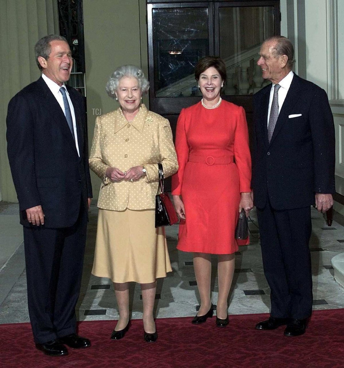 US President Bush (L) is greeted by Britain's Queen Elizabeth II (2ndL) and the Duke of Edinburgh as he arrives out of the rain with his wife, Laura, at Buckingham Palace for lunch, 19 July 2001. US president is on his first visit to the United Kingdom, before travelling on to the G8 summit in Genoa