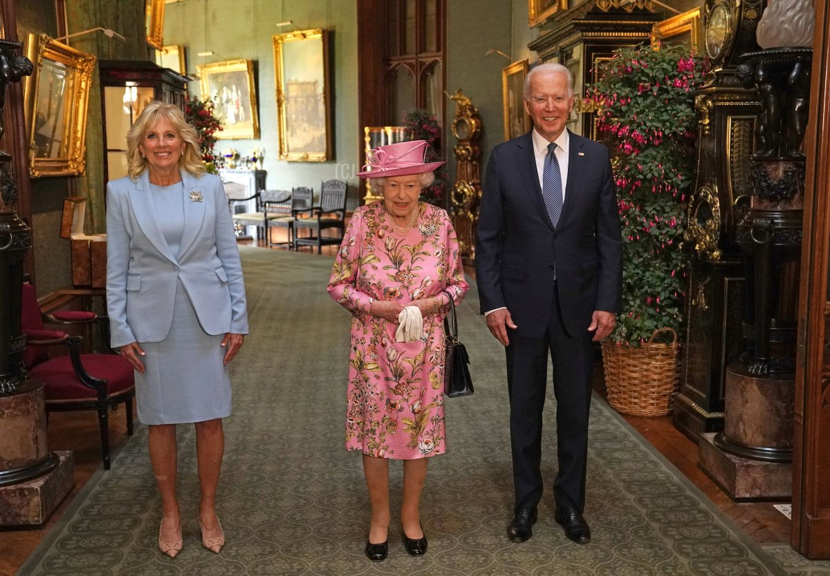 US President Joe Biden (R) and US First Lady Jill Biden (L) pose for a photograph with Britain's Queen Elizabeth II (C) in the Grand Corridor at Windsor Castle in Windsor, west of London, on June 13, 2021, before taking tea