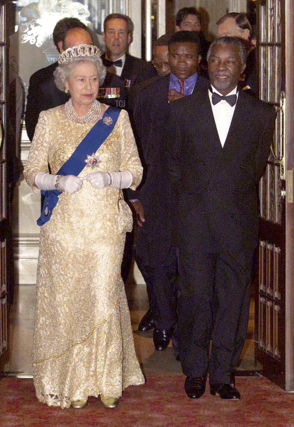 Britain's Queen Elizabeth II arrives with South African President Thabo Mbeki for a state banquet held for the Commonwealth Heads of Government, in Durban 12 November 1999