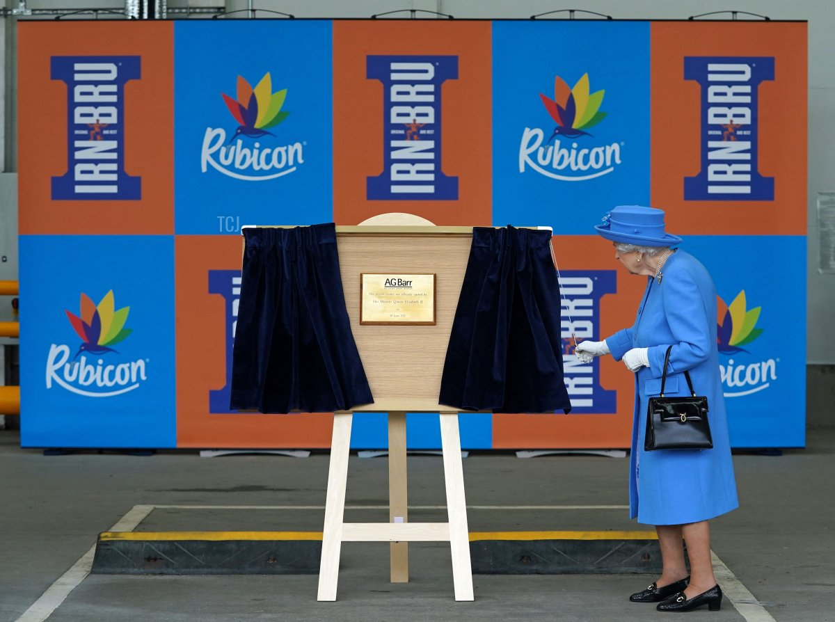 Britain's Queen Elizabeth II unveils a plaque during a visit to AG Barr's factory in Cumbernauld, east of Glasgow, where the Irn-Bru drink is manufactured on June 28, 2021