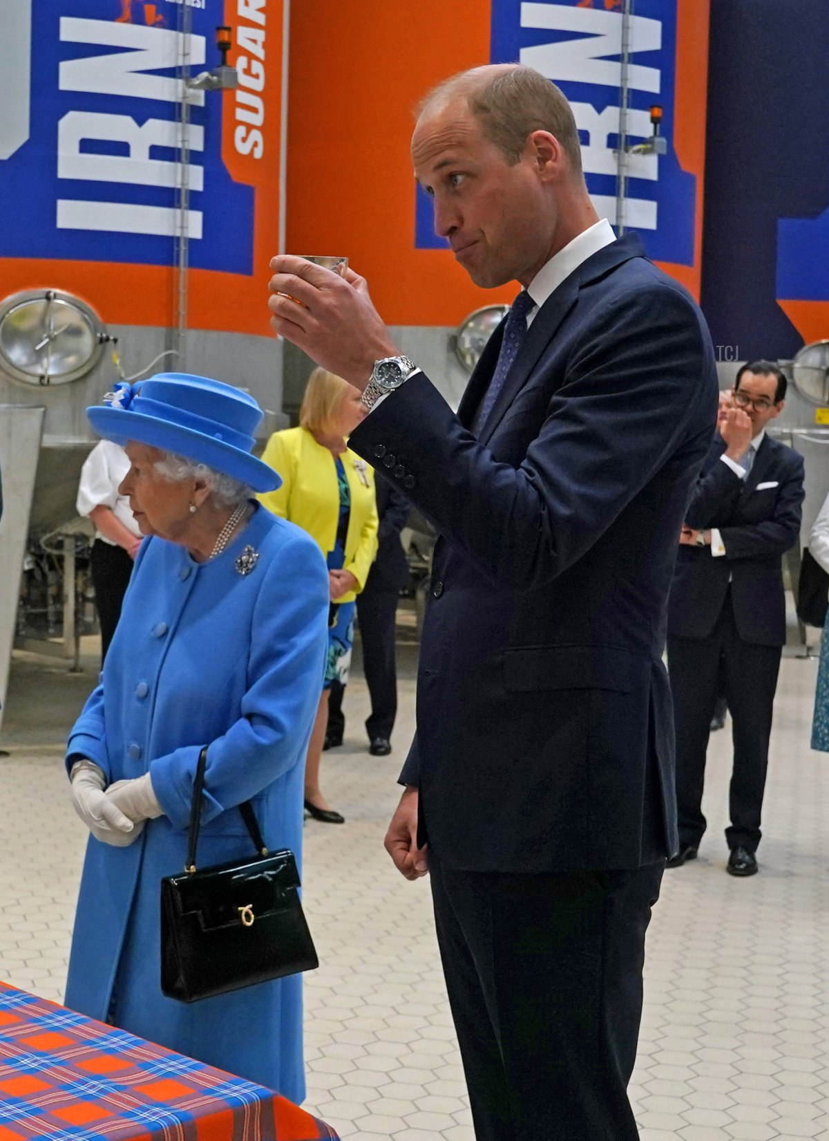 Britain's Prince William, Duke of Cambridge (R) reacts while sampling Irn-Bru as he and Britain's Queen Elizabeth II visit AG Barr's factory in Cumbernauld, east of Glasgow, where the Irn-Bru drink is manufactured on June 28, 2021
