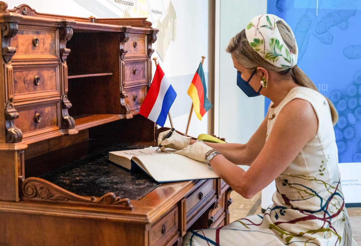 Queen Maxima of the Netherlands signs the Golden Book during a visit to the Robert-Koch-Institute (RKI, German national agency and research institute for disease control and prevention) on July 5, 2021 in Berlin