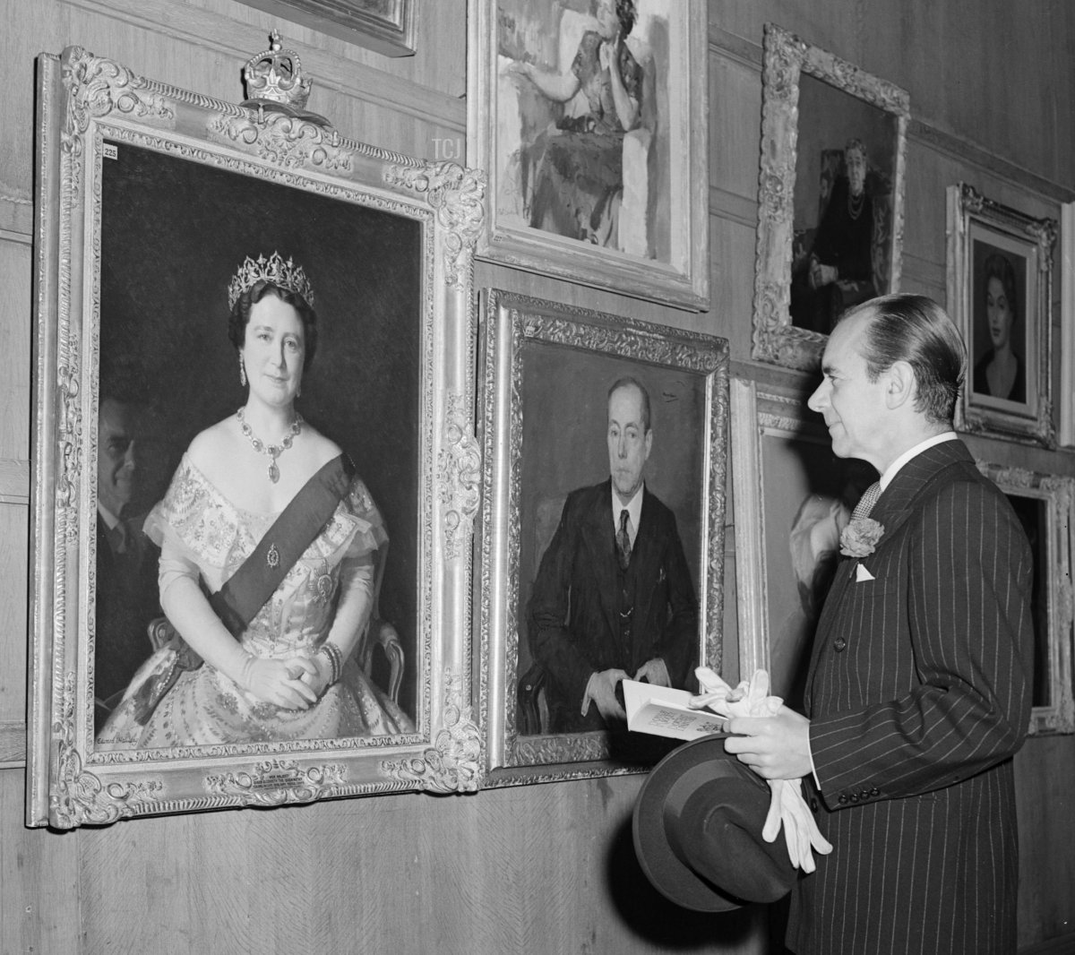 20th November 1953: British conductor Malcolm Sargent (1895 - 1967) examines the portrait of the Queen Mother by Edward I Halliday at the Annual Exhibition of the Royal Society of Portrait Painters at the Royal Institute Galleries, London