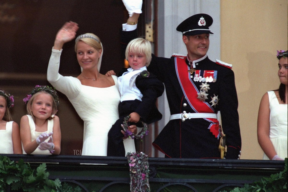 Norwegian Crown Prince Haakon, his bride Mette-Marit Tjessem Hoiby and her son Marius stand on the balcony of the Oslo Cathedral August 25, 2001 after their wedding