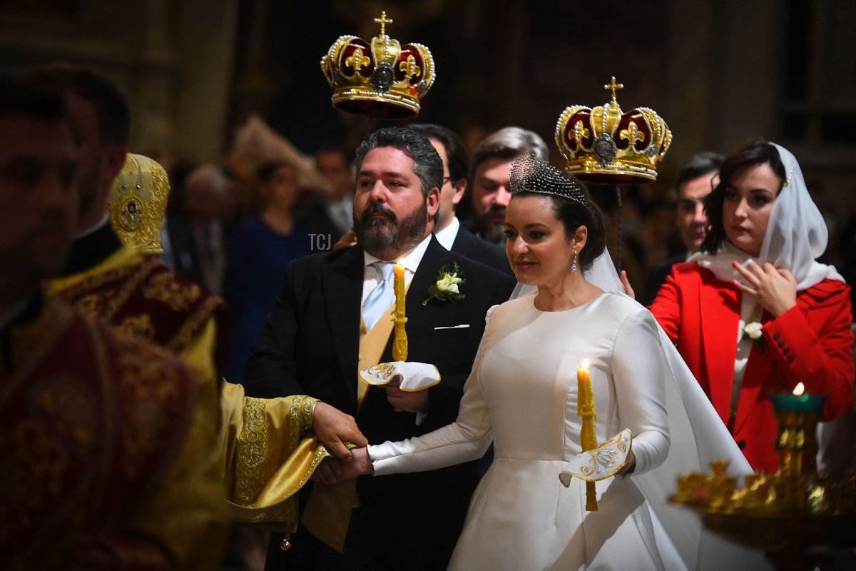 Grand Duke George Mikhailovich Romanov and Victoria Romanovna Bettarini hold candles as they react during their wedding ceremony at Saint Isaac's Cathedral in Saint Petersburg, on October 1, 2021