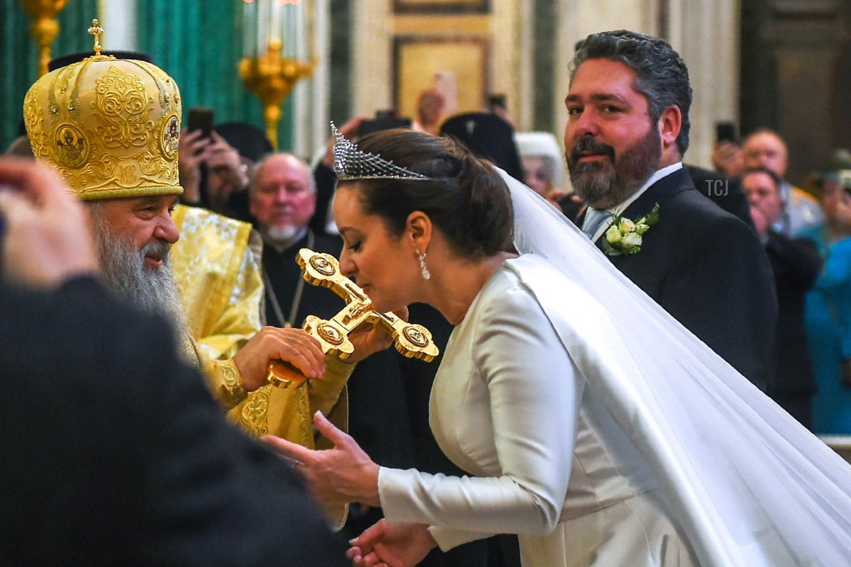 Victoria Romanovna Bettarini kisses a cross as Grand Duke George Mikhailovich Romanov looks on during their wedding ceremony at Saint Isaac's Cathedral in Saint Petersburg, on October 1, 2021