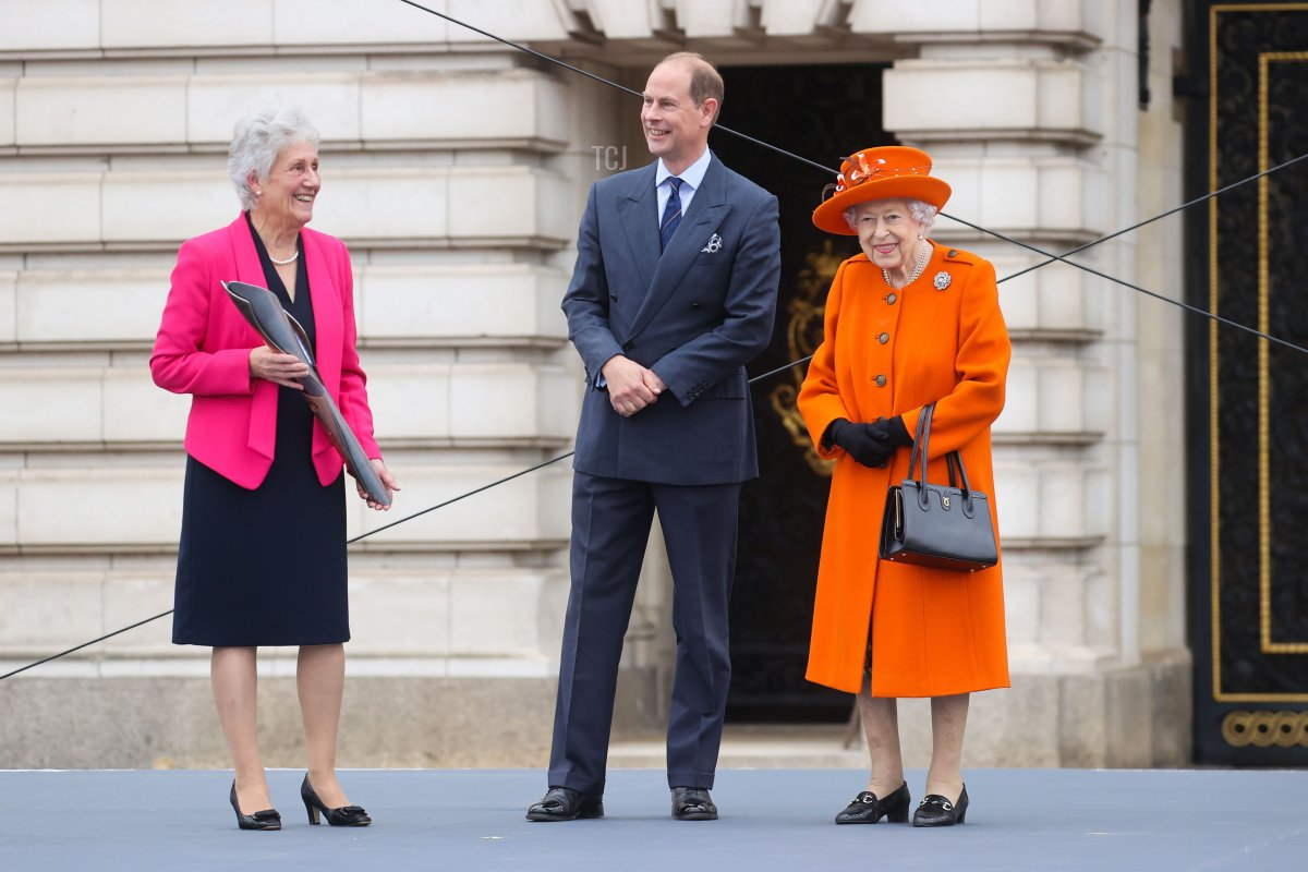 Queen Elizabeth II, Prince Edward, Earl of Wessex and Dame Louise Martin, President of the Commonwealth Games Federation speak on stage during the launch of The Queen's Baton Relay for Birmingham 2022, the XXII Commonwealth Games at Buckingham Palace on October 07, 2021 in London, England