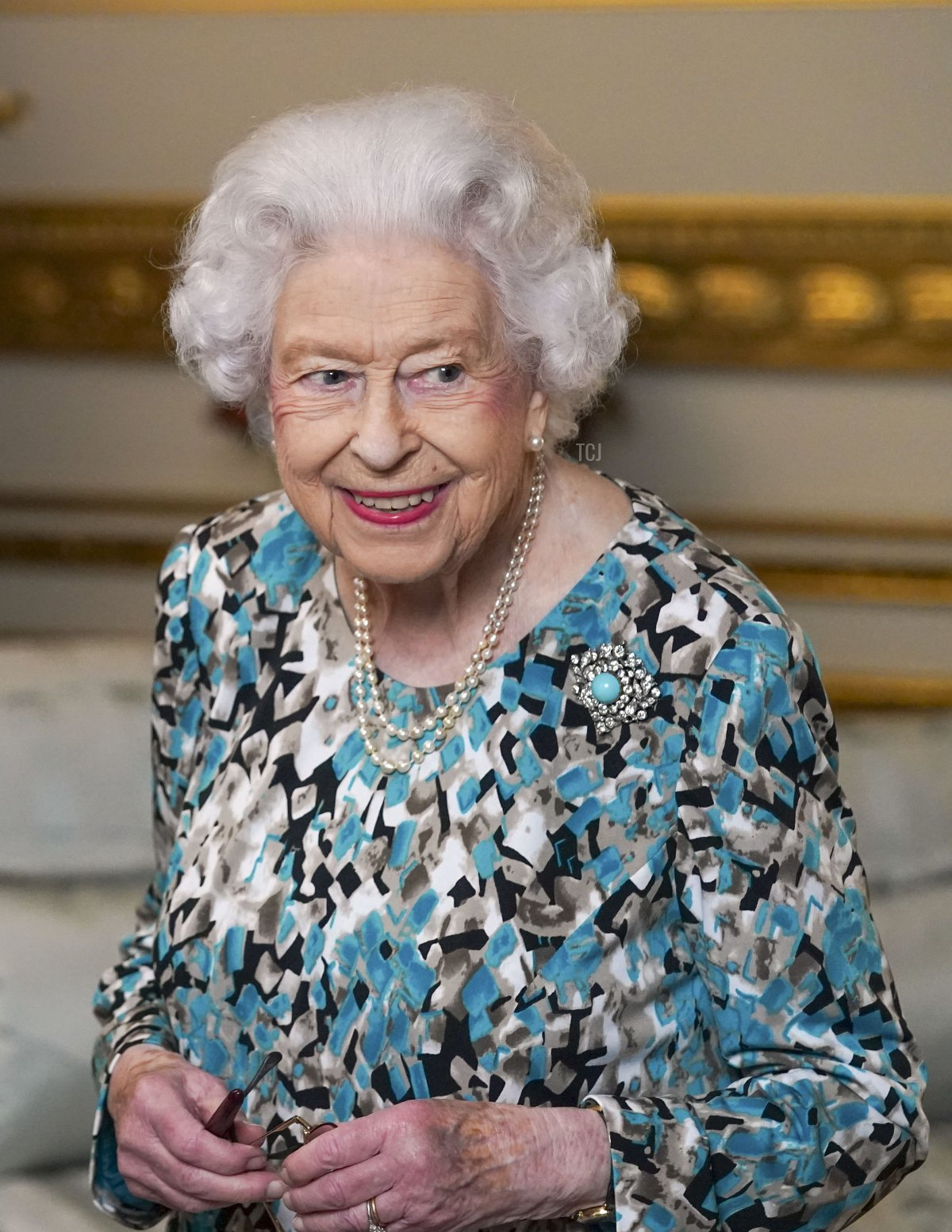 Queen Elizabeth II looks at the Birmingham 2022 Commonwealth Games Baton during the Baton Relay for Birmingham 2022, the XXII Commonwealth Games at Buckingham Palace on October 7, 2021 in London, England