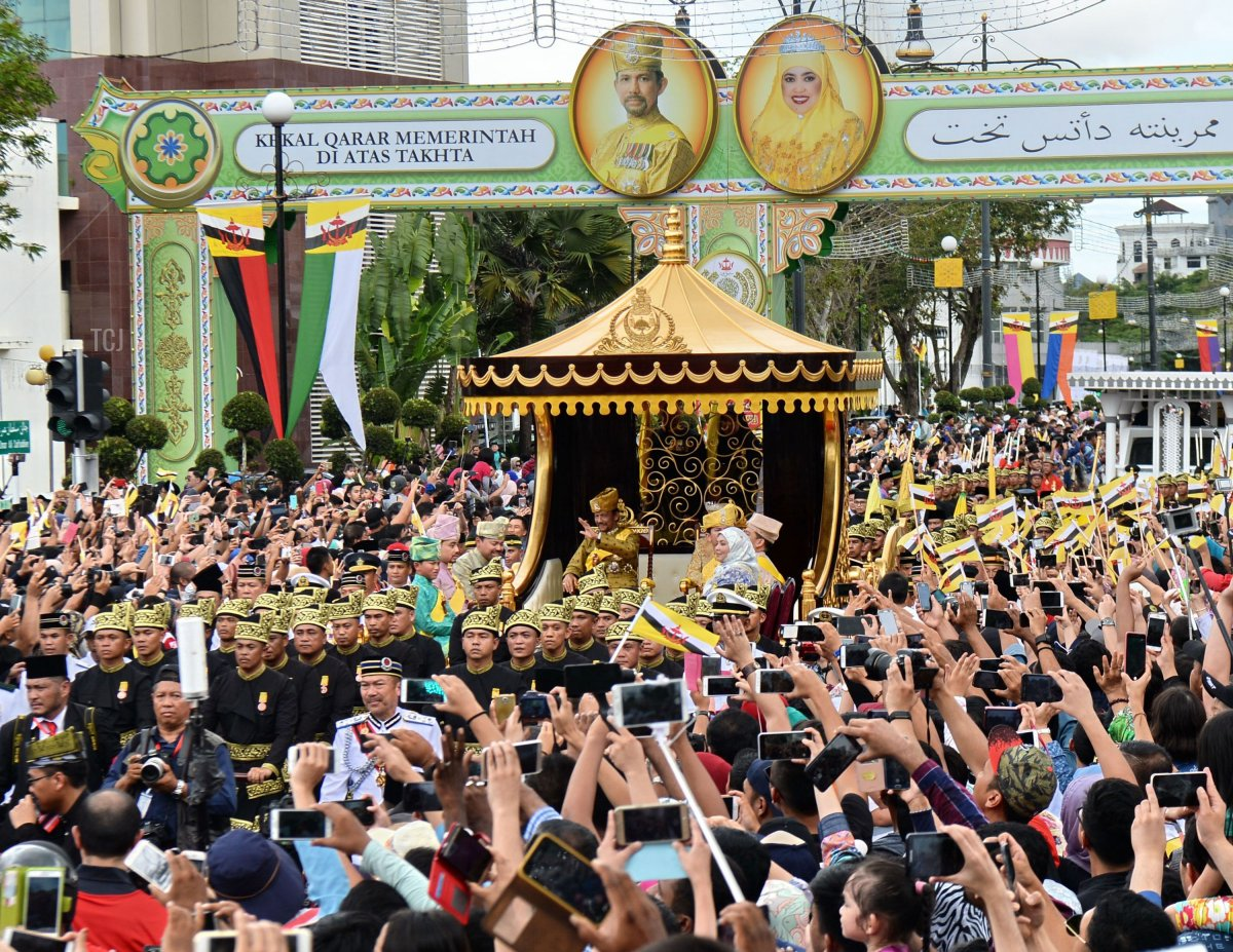 Brunei's Sultan Hassanal Bolkiah (center-L) and Queen Saleha (centre-R) wave from the royal chariot during a procession to mark his golden jubilee of accession to the throne in Bandar Seri Begawan on October 5, 2017