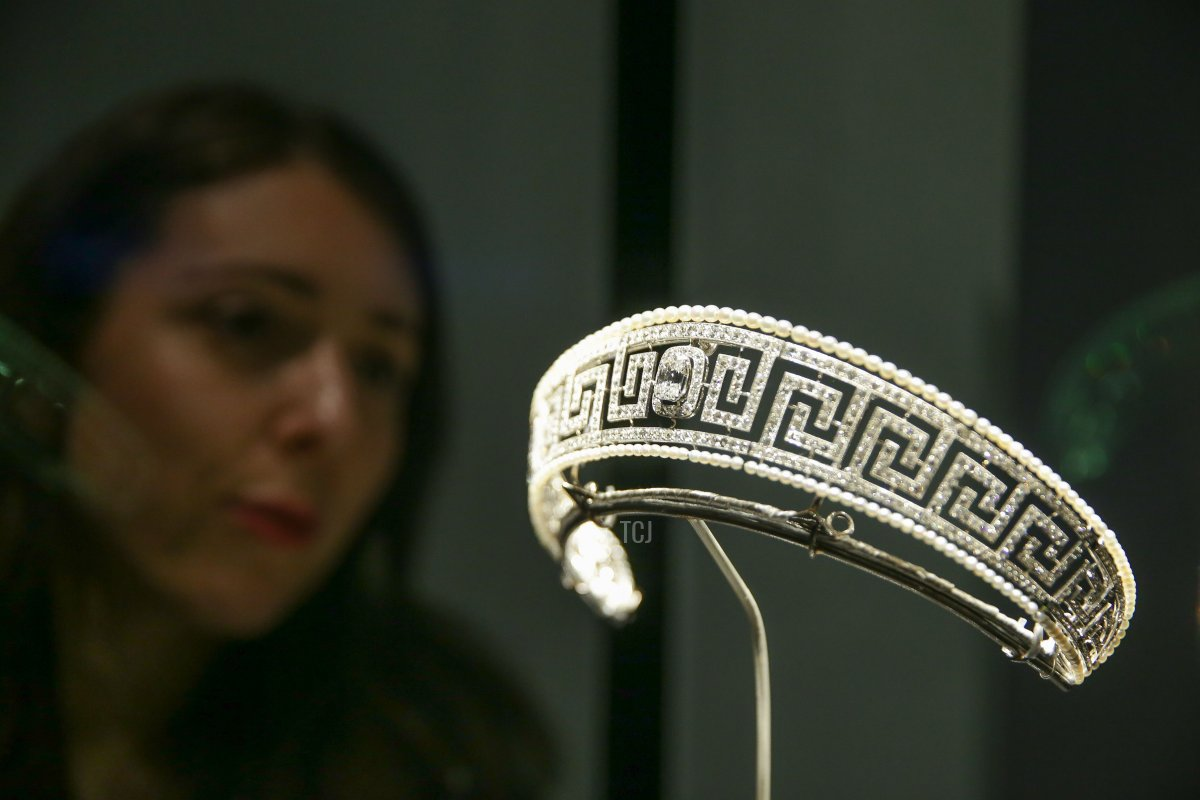 A museum employee poses next to a diamond and pearl Cartier tiara saved from the Lusitania presented at a new exhibition 'Ocean Liners: Speed and Style' at the Victoria and Albert Museum in west London on January 31, 2018