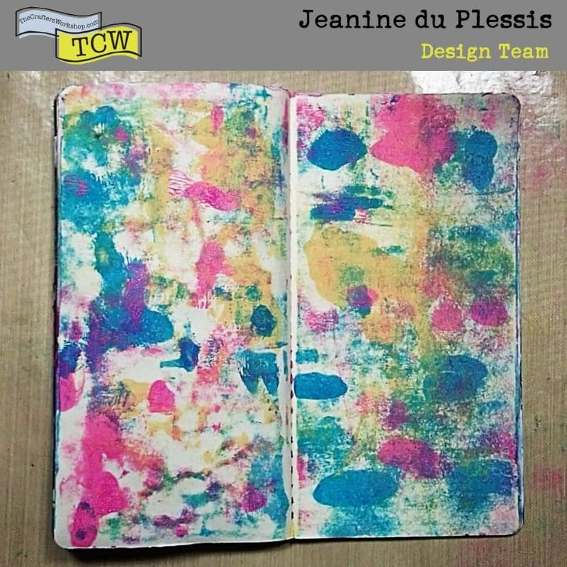 Photo of pink, blue and peach paint brayered onto the page in patches