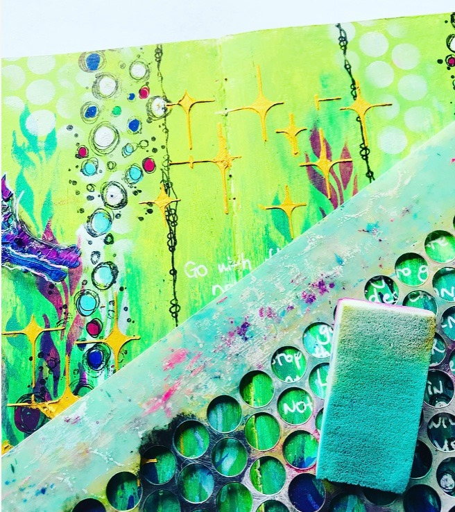 adding details to the art journal page with stamps and paint markers