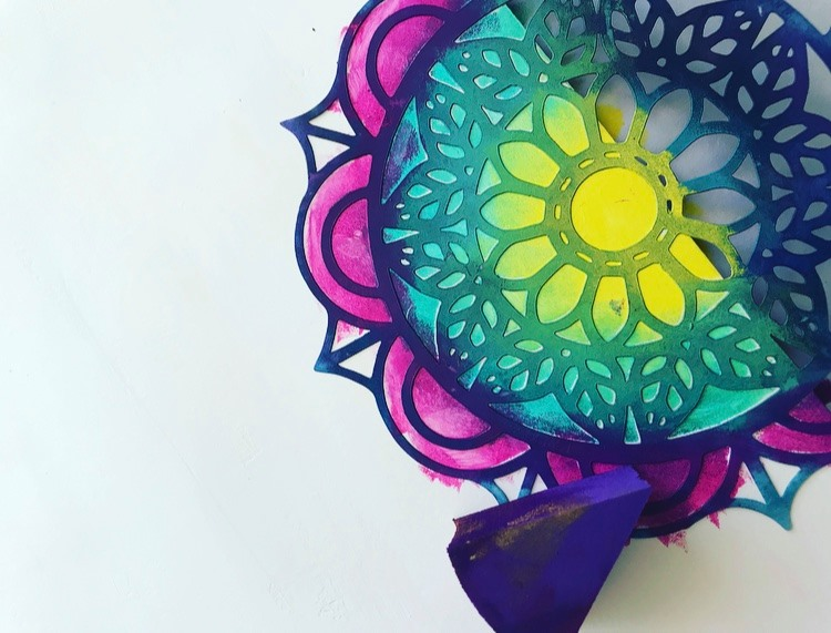small leaf emblem stencil with paint sponged over the top to create a rainbow mandala effect
