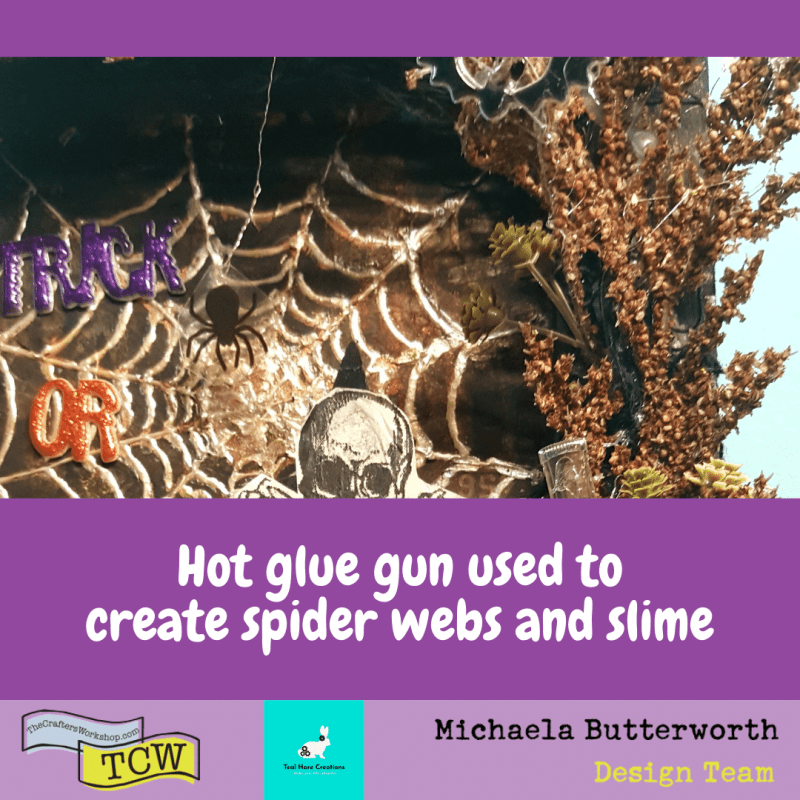 Close up image showing the glue gun spider webs and slime globs. The spider is printed on clear acetate, and hangs from silver bullion wire, suspended over the web for a 3D effect.