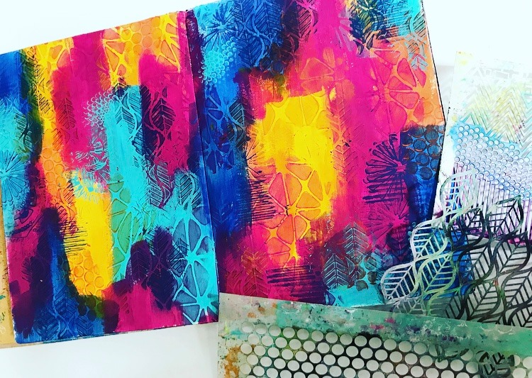 adding stencil patterns to a rainbow background art journal page