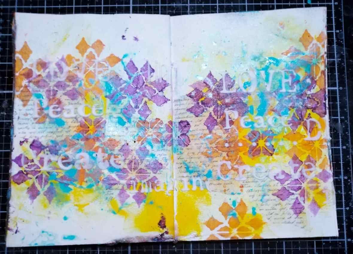 Background texture of art journal spread with acrylic mediums and stencils